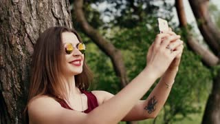 Beautiful brunette woman with red lips takes selfie near a tree, uses her smartphone. Modern technology. Slow mo