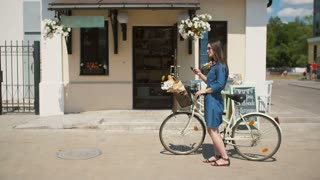 Beautiful brunette young woman wearing sunglasses standing near cute building with her bike talking on the phone