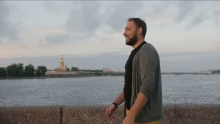 Beautiful couple in love swirling around, smiling, kissing The Peter and Paul Fortress, river at the background, slow mo