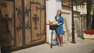 Beautiful girl standing in the street with a bike with basket talking on the phone and smiling, 4k
