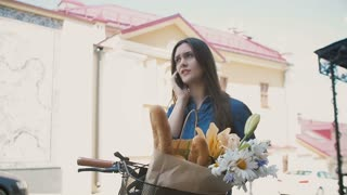 Beautiful girl standing in the street with a bike with basket talking on the phone and smiling, slow mo