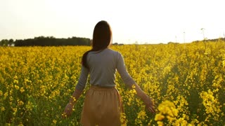 beautiful girl walks through field at sunset