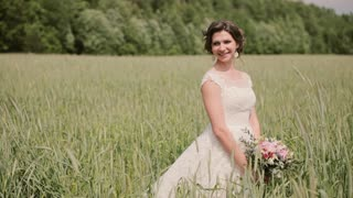 Beautiful smiling bride in a wheat field enjoys her wedding day. Hair and cones sway in the wind.