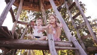 Beautiful smiling girl and boy siblings playing with ball outdoor on tree house together with their parent on sunny day