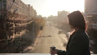 Beautiful woman drinking coffee on a city bridge