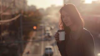 Beautiful woman drinking coffee on a city bridge