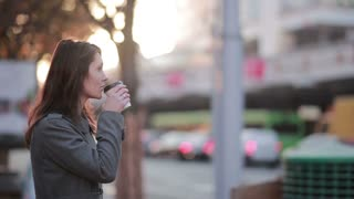 Beautiful woman drinking coffee on the street