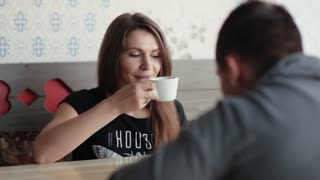 Beautiful woman has cup of coffee or tea and chocolate as she talks with a man in cafe. She smiles, enjoys good company.