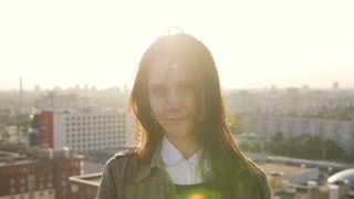 beautiful woman standing on the roof of high-rise building at sunset looking at the camera. Wind blows her hair Slow mo