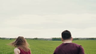 Beautiful woman teases her lover running away in a field, he chases. Happy lovers have fun. Slow mo, steadicam shot