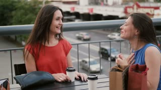 Beautiful women drinking coffee communicate in a cafe with a view of the traffic, talking after shopping. 4k