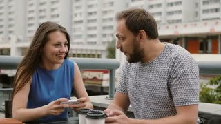 beautiful young couple playing as a team game online on their smartphones. they win, celebrate the victory, give five 4K