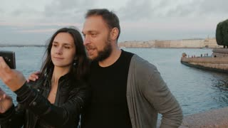 Beautiful young couple taking selfie on the background of river and the city. St. Petersburg. 4K