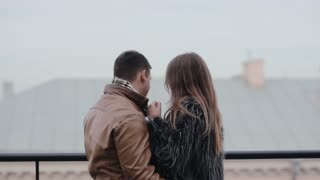 Beautiful young couple tenderly hugging, kissing each other. Harmony in relationship. Loving couple on a roof.