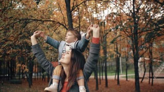 beautiful young mother holds on the shoulders a cute little son, the boy point the finger at something in autumn park 4k