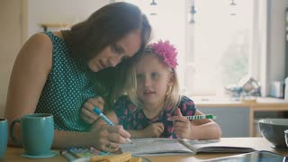 Beautiful young mother is helping her blond little daughter to colour a picture with felt pens. Slow mo