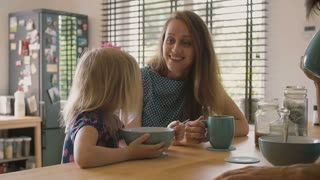 Beautiful young mother is talking to her cute blond daughter at breakfast and smiling. Slow mo
