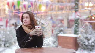 Beautiful young woman drinking hot tea during Christmas Fair