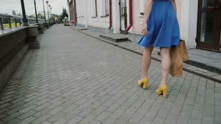Beautiful young woman in blue dress walking in the city with shopping bags, looks around, slow mo stedicam shot