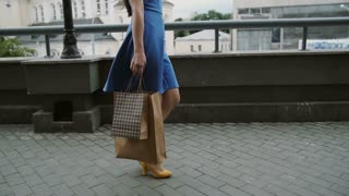 Beautiful young woman in blue dress walking in the city with shopping bags, slow mo stedicam shot
