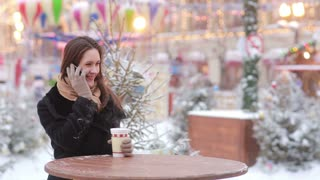 Beautiful young woman talking on the phone and drinking hot tea during the Christmas Fair