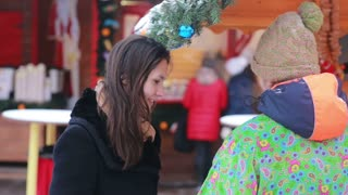 Beautiful young woman talking with the seller at the Christmas Fair in Moscow, Russia.