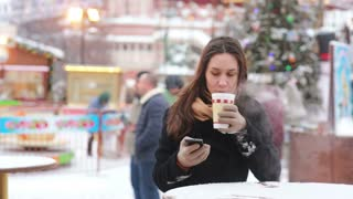 Beautiful young woman using a smartphone and drinking hot tea during the Christmas Fair