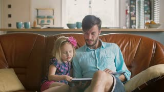 blond little girl is choosing a story that her loving father will read on the sofa. Slow motion