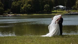 bride and groom standing by the river. slow motion