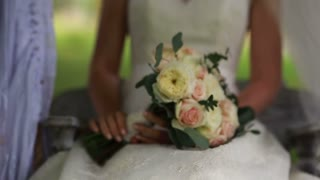 bride on a swing while holding a bouquet in hands