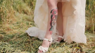 Bride shows a tattoo on her leg under a wedding dress. Surprising view of a colourful tattoo with a picture of a woman