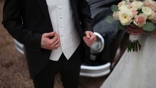 bride with a bouquet and groom near a retro car
