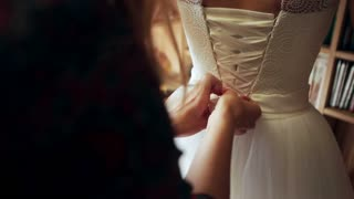 Bridesmaids buttoning on wedding dress