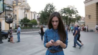 Brunette beautiful young woman in a denim dress walking in the street. She uses her smartphone. Slow mo, steadicam shot