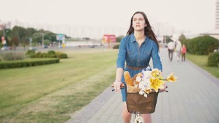 Brunette girl cycling with flowers in a basket and exploring the city, slow mo, steadicam shot