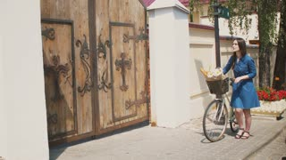 Brunette girl in a dress throws back her hair and walks her bike with flowers in a basket, 4k, steadicam shot
