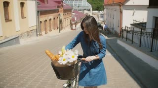 Brunette girl in a dress throws back her hair and walks her bike with flowers in a basket, slow mo, steadicam shot