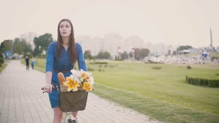 Brunette girl on a bike with flowers and French bread in a basket while cycling in the city, slow mo, steadicam shot