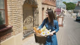 Brunette girl smiling to camera walks her bike with flowers and French bread in a basket, slow mo, steadicam shot