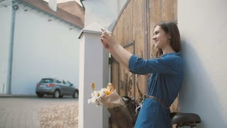 Brunette girl taking selfie, standing near old building with a bike with flowers in a basket, slow mo