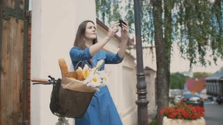 Brunette girl touching her hair, taking selfie, standing with a bike with flowers and bread in a basket, slow mo