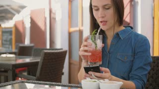 Brunette girl uses smart phone while sitting outside in a cafe, drinking and enjoying a cool drink from straw tube. 4k,