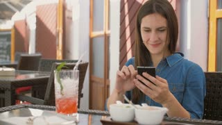 Brunette girl uses smart phone while sitting outside in a cafe, smiles and laughs. 4k,