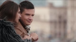 Brunette man and woman talk standing on a roof or a balcony. Focus shifts to a busy street in a city.