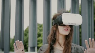 Brunette woman girl with waving hair uses virtual reality glasses in the urban space. 4k