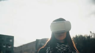 Brunette woman uses 3D Virtual Reality headset in rear light at sunset 4k