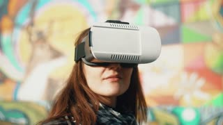 Brunette woman uses 3D Virtual Reality headset on bright background outdoors 4k