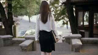 Businesswoman walking in the old city. slow mo