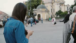 Busy street. Backview of a pretty woman walking, using smartphone. She flips her long hair back. Slow mo, steadicam shot