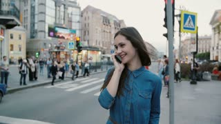 Busy street. Pretty woman talks on the phone, hangs up. People cross the road at the background. Slow mo